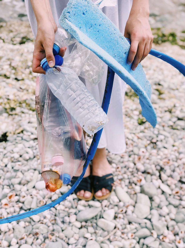 woman collecting disposable plastics from shoreline