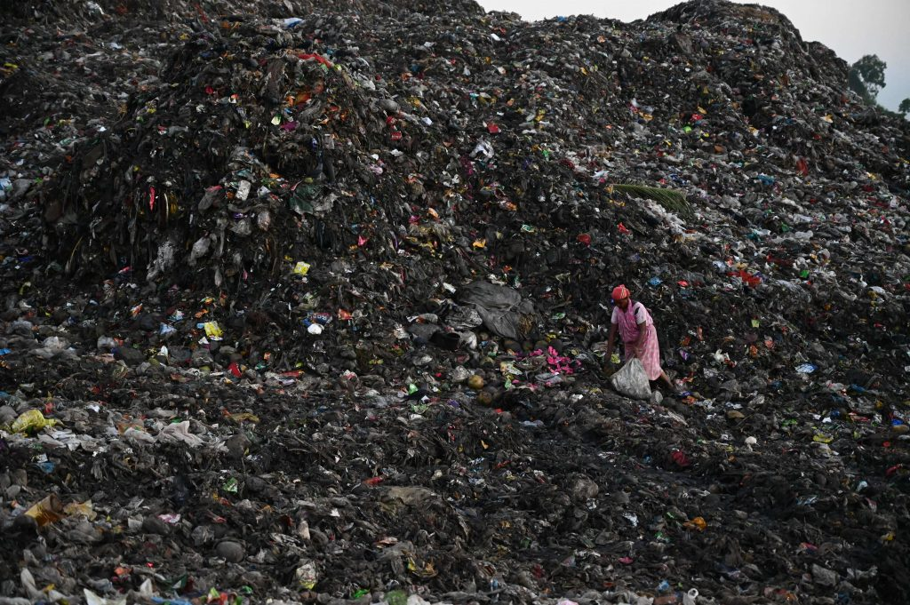 person climbing mountain of trash at giant landfill