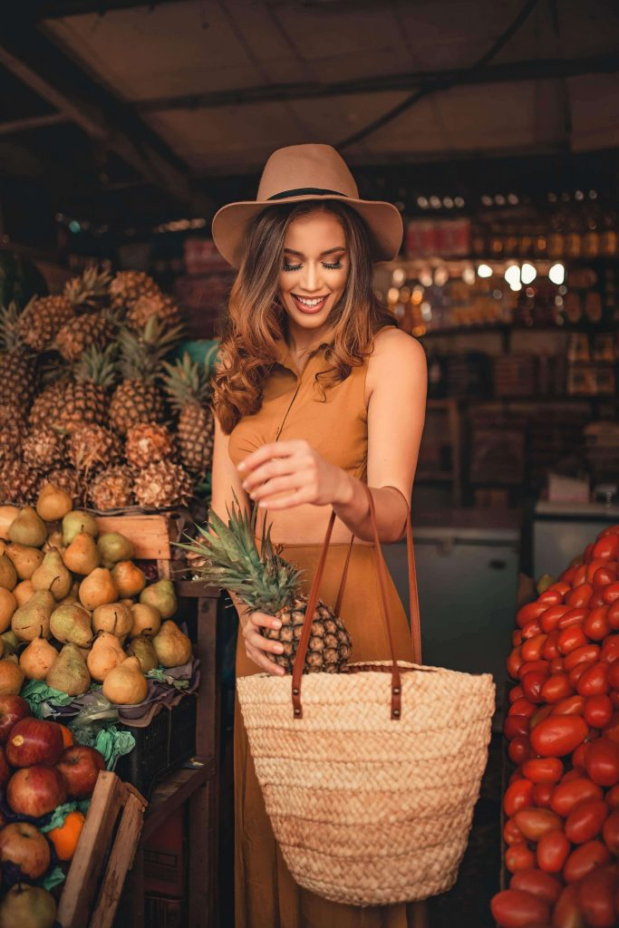 woman putting pineapple in bag at farmer's market