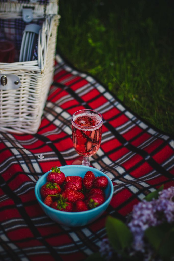 zero waste valentine's day picnic basket with glass of wine and bowl of strawberries