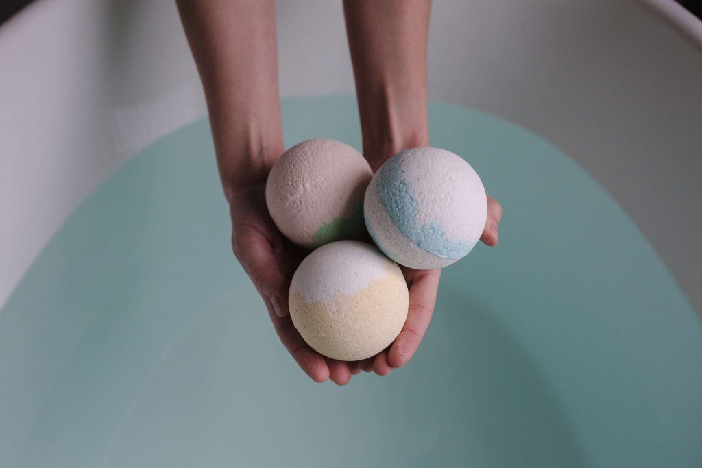 person holding bath bombs over tub