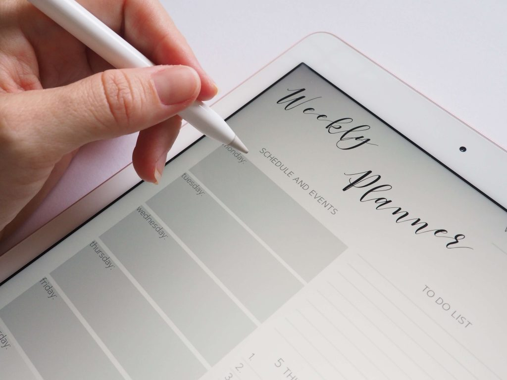 """iPad and stylus showing a """"weekly planner"""" on the screen for planning a zero waste shopping trip"""