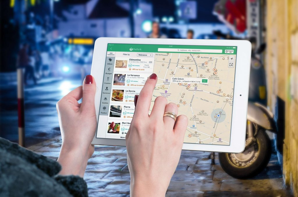 woman holding iPad deciding on route with Maps app which saves emissions for a zero waste shopping trip