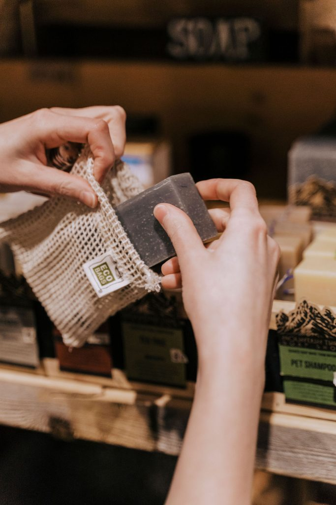 putting an unwrapped soap bar into my mesh bag at a zero waste store