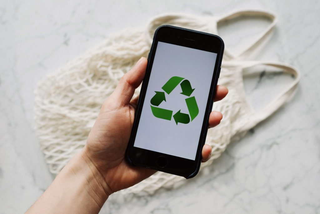 person holding phone with recycling symbol of arrows on it, representing researching what can't be recycled and what can