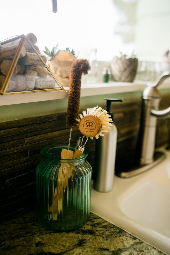 standing wooden dish brushes in a vase by the sink