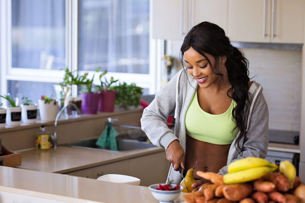 woman cutting into pear on kitchen counter