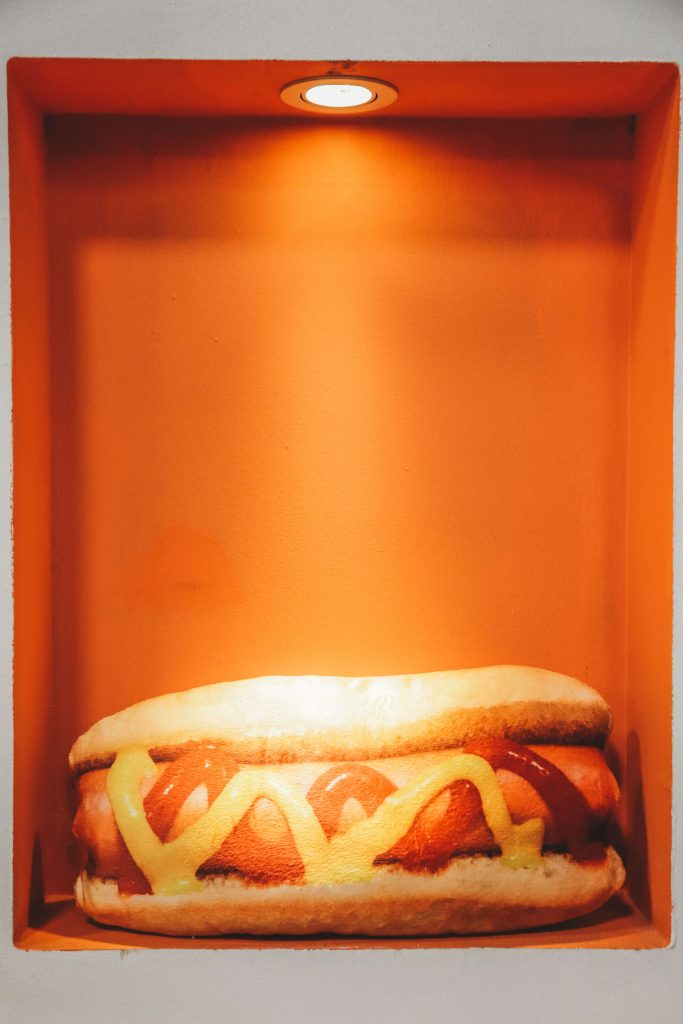 hot dog in a box with light shining on it