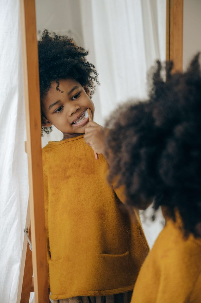 little kid brushing teeth and smiling in mirror