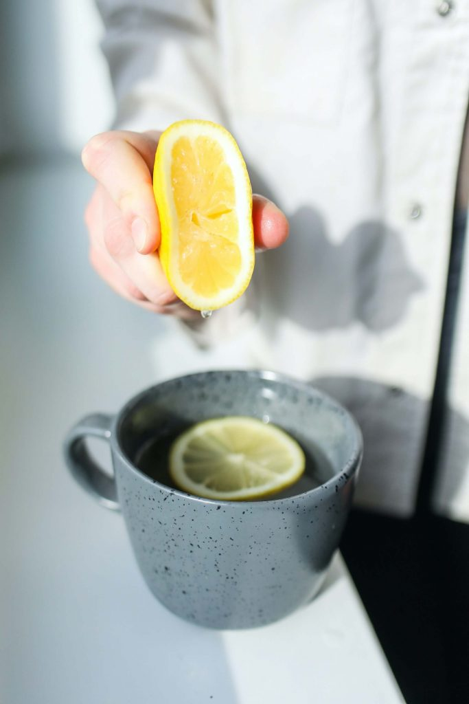 person squeezing lemon into mug to use every bit of those food scraps