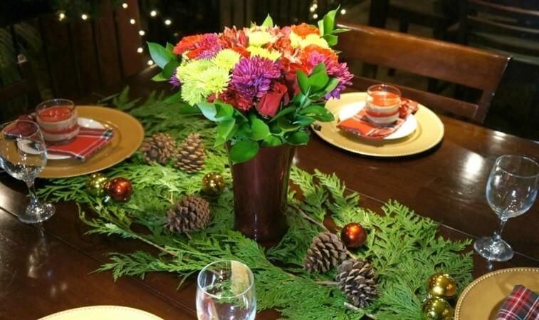 green holiday party decor with flowers and pinecone arrangements on tables