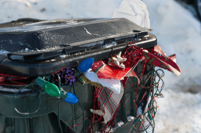 trash can overflowing with holiday party decorations and waste