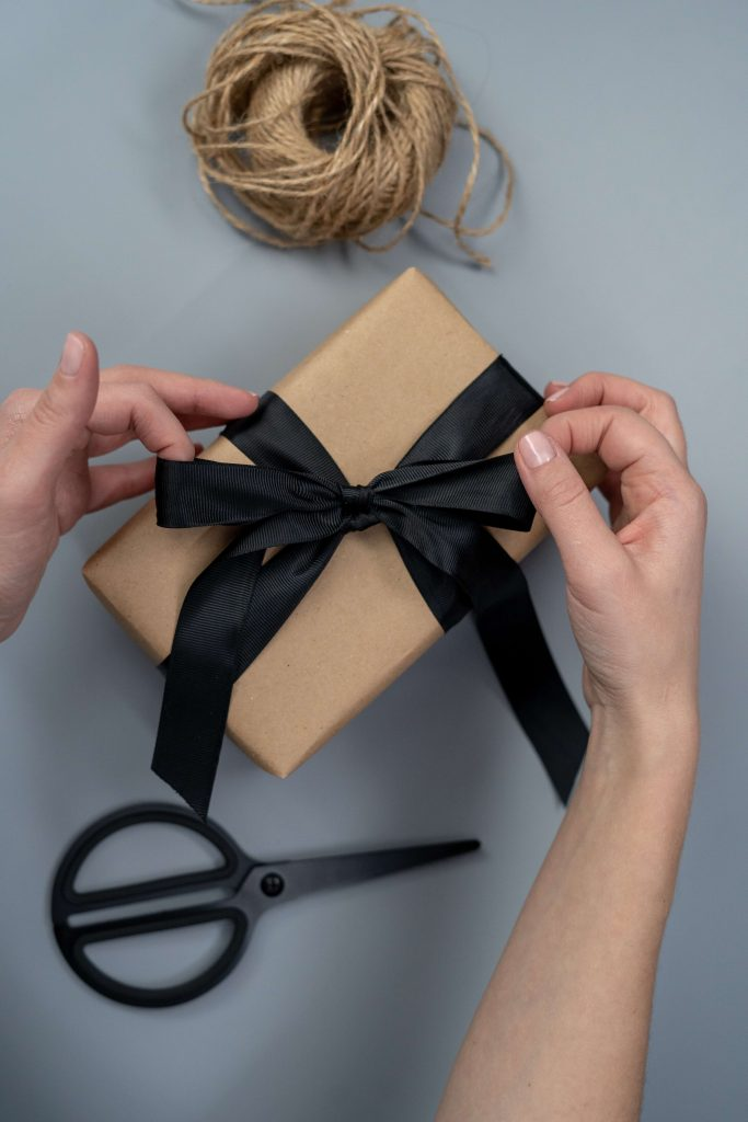 person wrapping a gift with brown paper and a black bow for a green holiday party