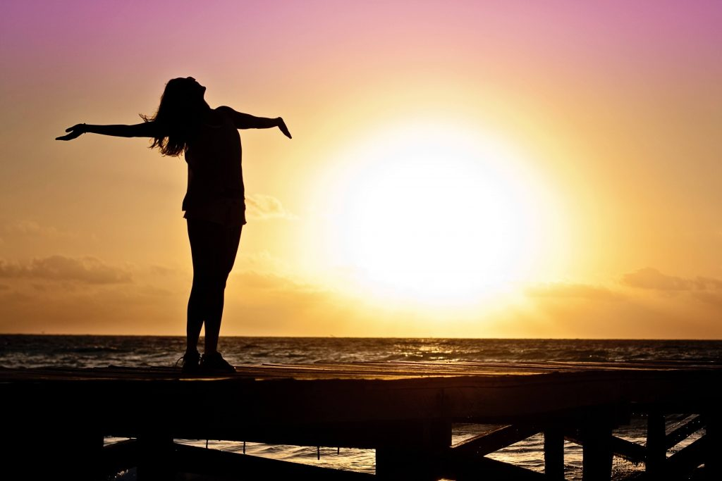 woman happily spreading her arms and looking to the sky with the sun setting over the ocean