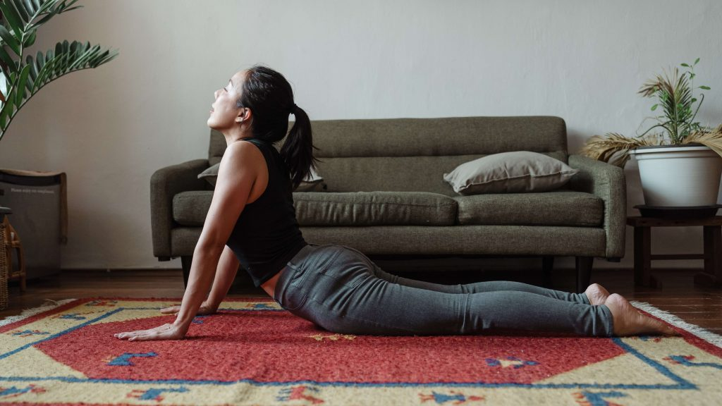 woman practicing mental minimalism through mindful yoga practice on rug