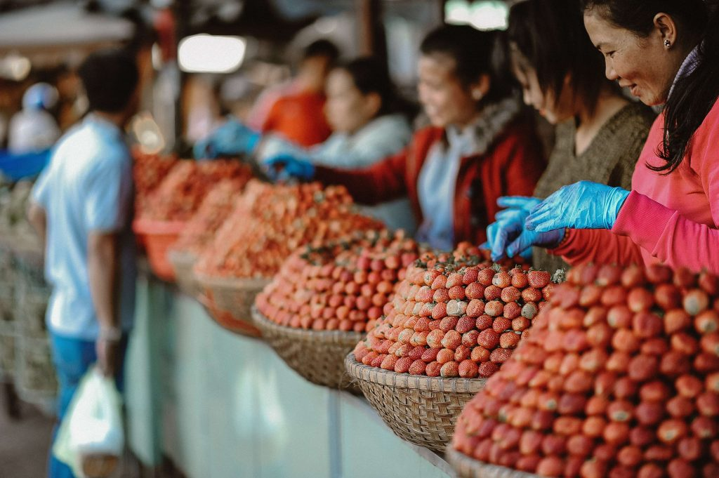 man shopping at local market with women standing by baskets of strawberries