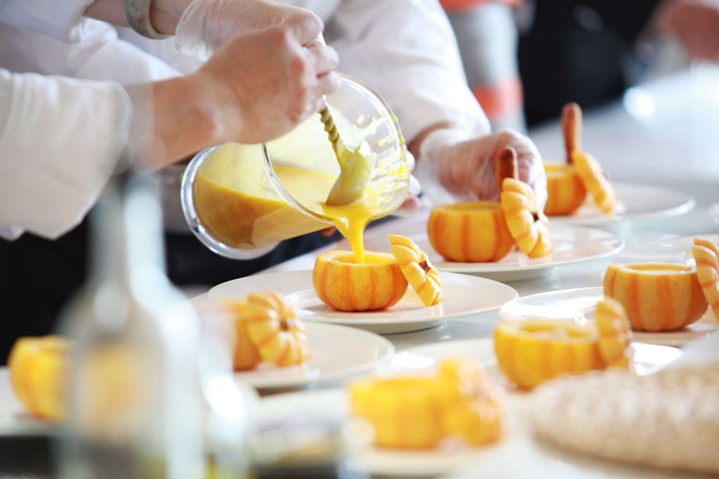 caterers pouring soup into pumpkin bowls on white plates