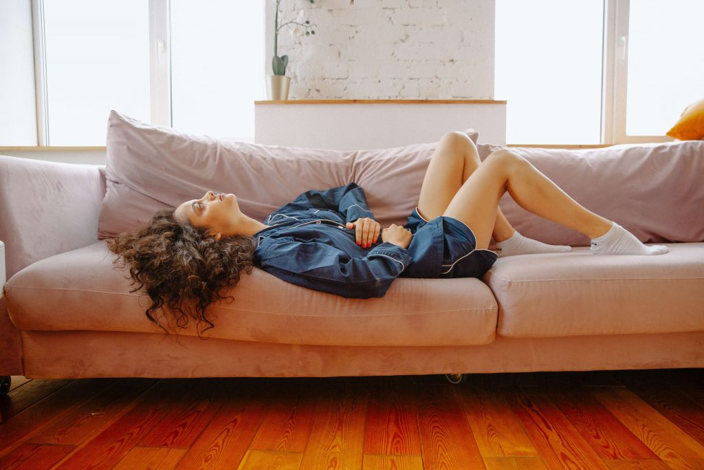 woman laying on couch holding stomach with menstrual cramps