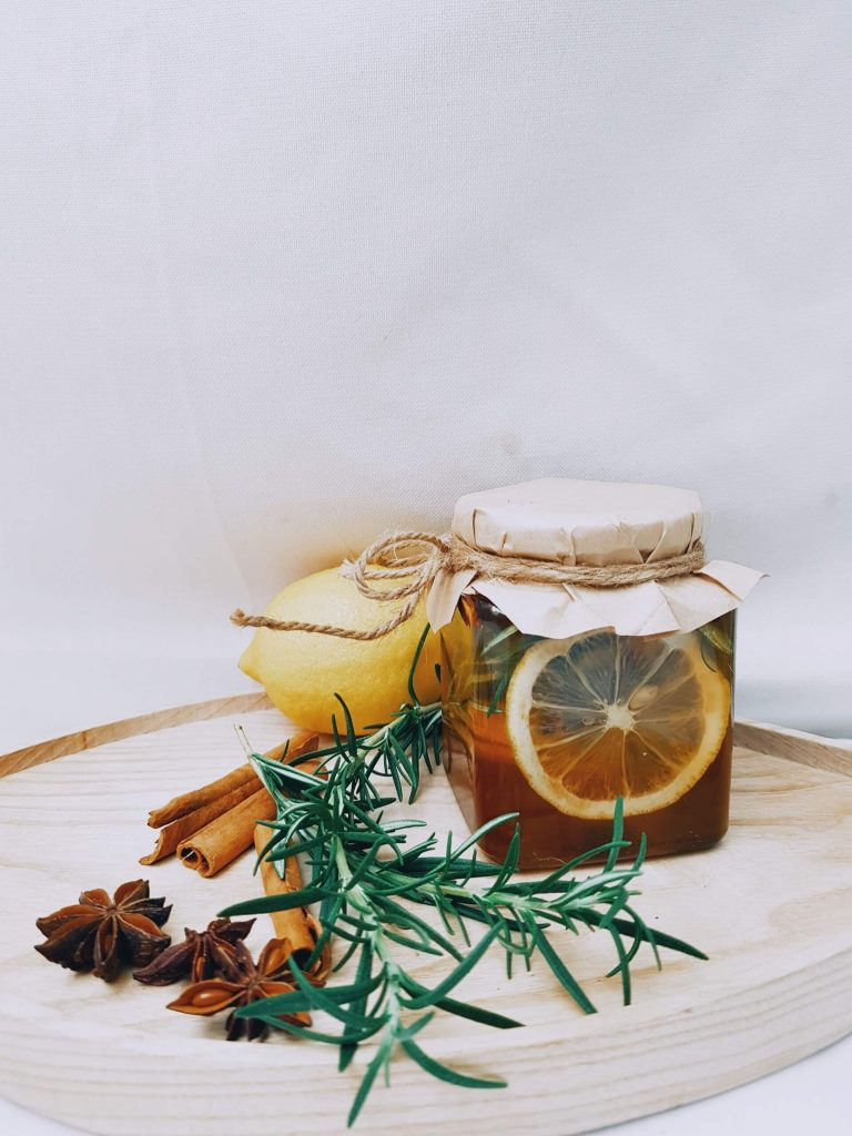 gift giving a homemade spiced tea in a glass jar sitting on wooden cutting board with lemon, cinnamon sticks, and herbs