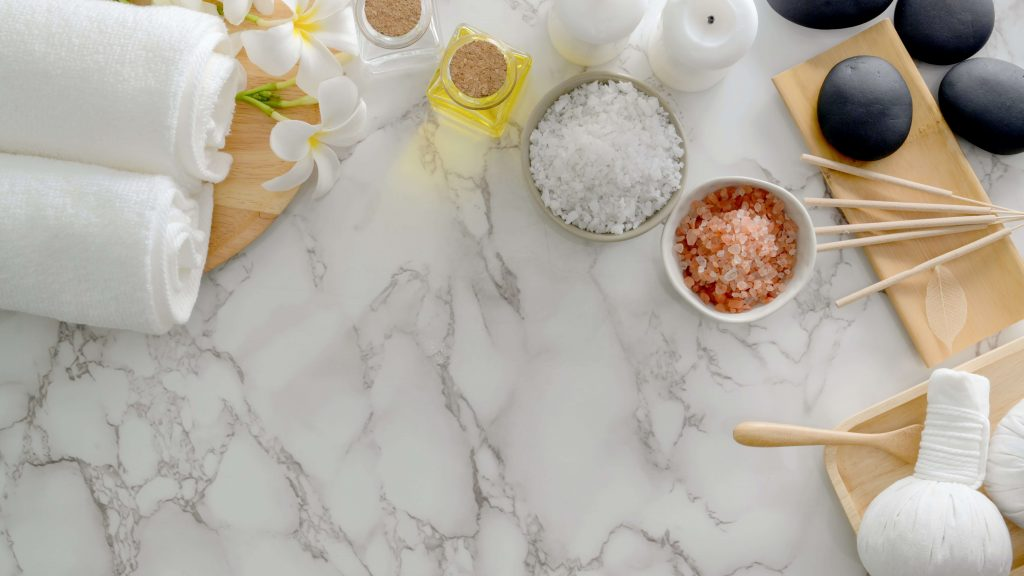 self-care items like towels, candles, bath salts, and oils on a marble countertop