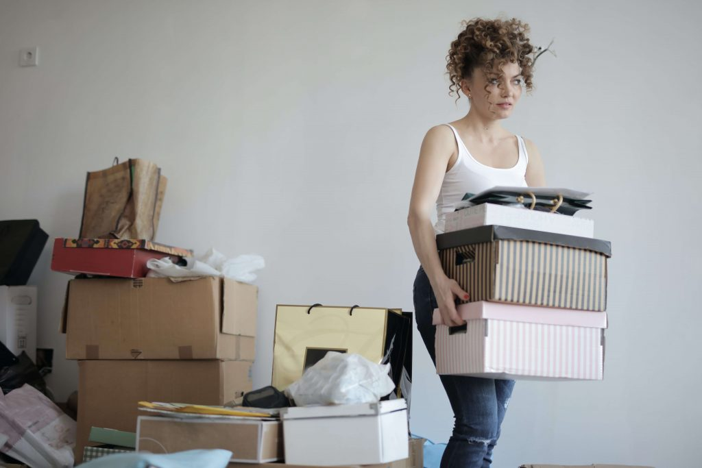 woman moving boxes and shopping bags cluttering her room