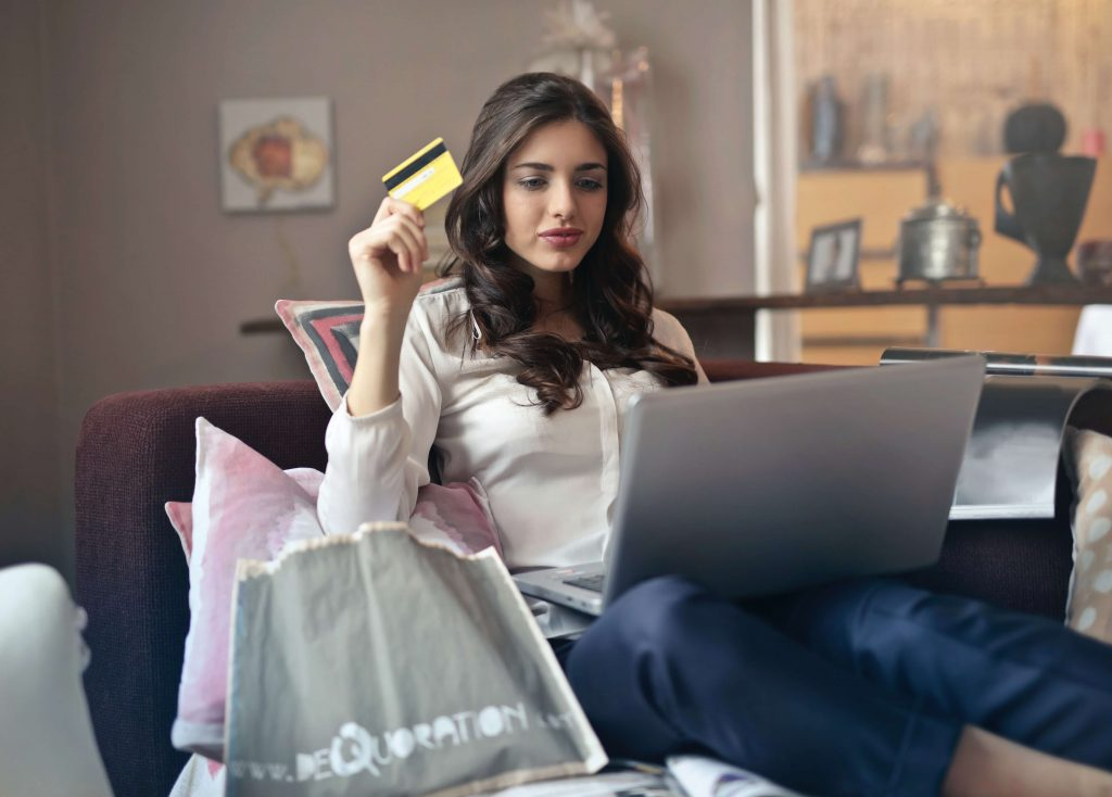 another woman trying to be a conscious consumer, holding her credit card while looking at her computer