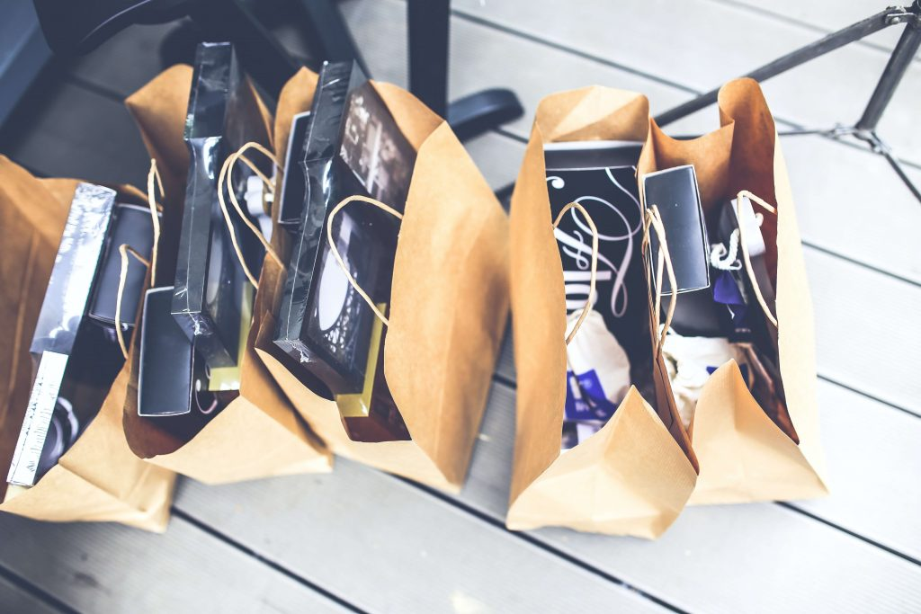 row of five paper shopping bags filled with various purchases