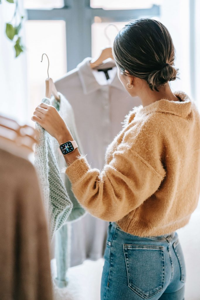 woman trying to be a conscious consumer by comparing two shirts in her hands while debating purchase