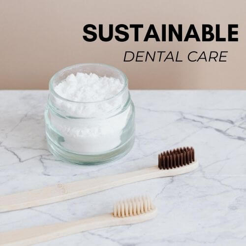 glass jar of toothpaste on marble countertop with two bamboo toothbrushes